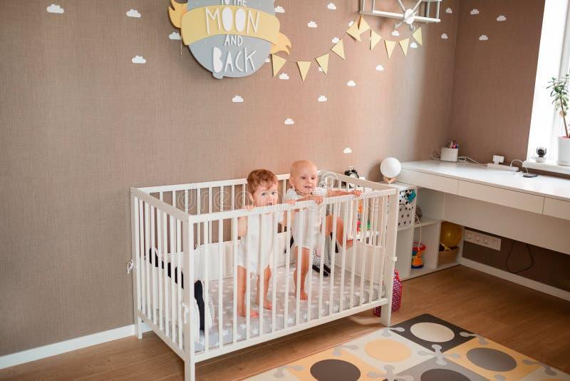Милые маленькие младенцы смотря из кровати стоковые фото