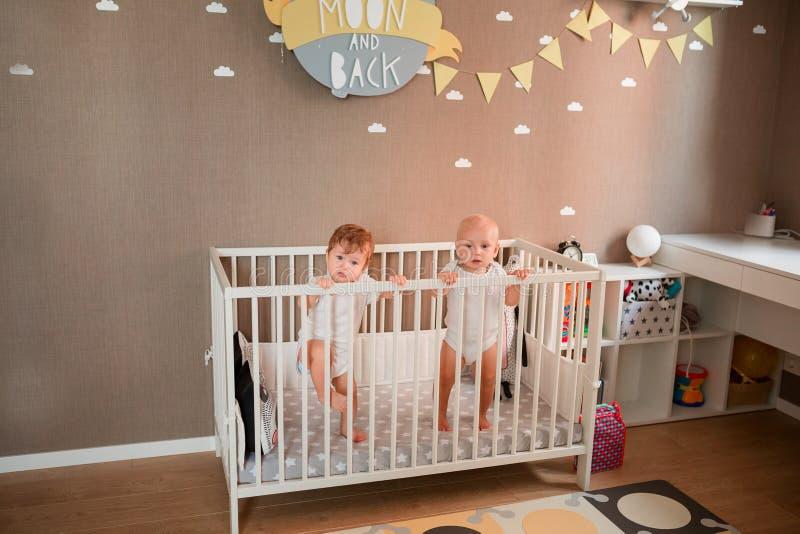 Милые маленькие младенцы смотря из кровати стоковые изображения