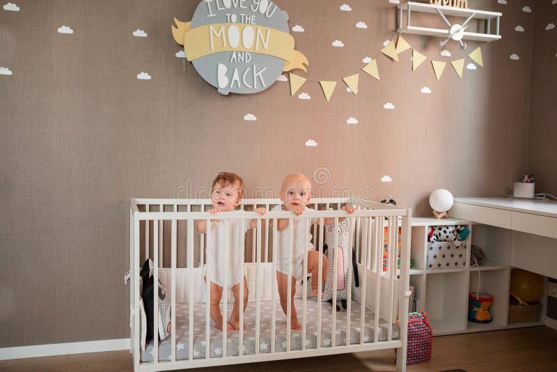 Милые маленькие младенцы смотря из кровати стоковые изображения rf