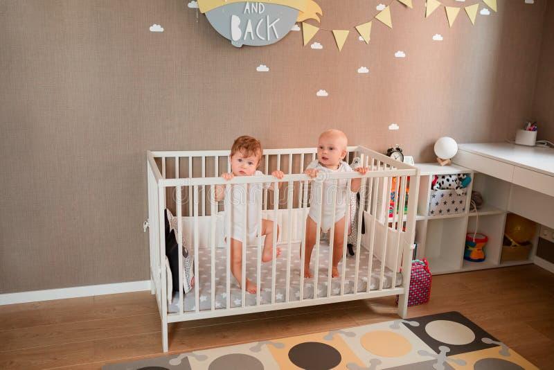 Милые маленькие младенцы смотря из кровати стоковое изображение rf