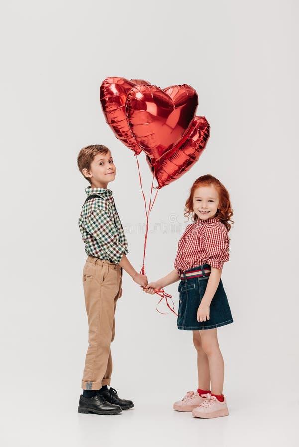 милые маленькие ребеята держа сердце сформировали воздушные шары и усмехаться на камере стоковые изображения rf