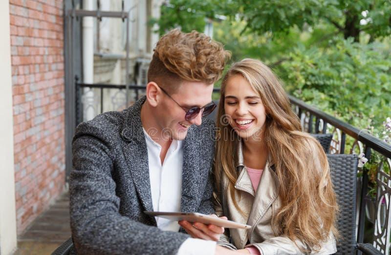 Милые молодые влюбчивые пары с цифровой таблеткой на запачканной предпосылке новая технология принципиальной схемы стоковые изображения