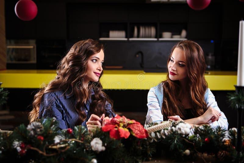 Милые молодые женщины близнецов совместно в комнате кухни, вскользь домашнем стиле, украшениях рождества Нового Года стоковые фото