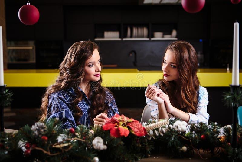 Милые молодые женщины близнецов совместно в комнате кухни, вскользь домашнем стиле, украшениях рождества Нового Года стоковые изображения