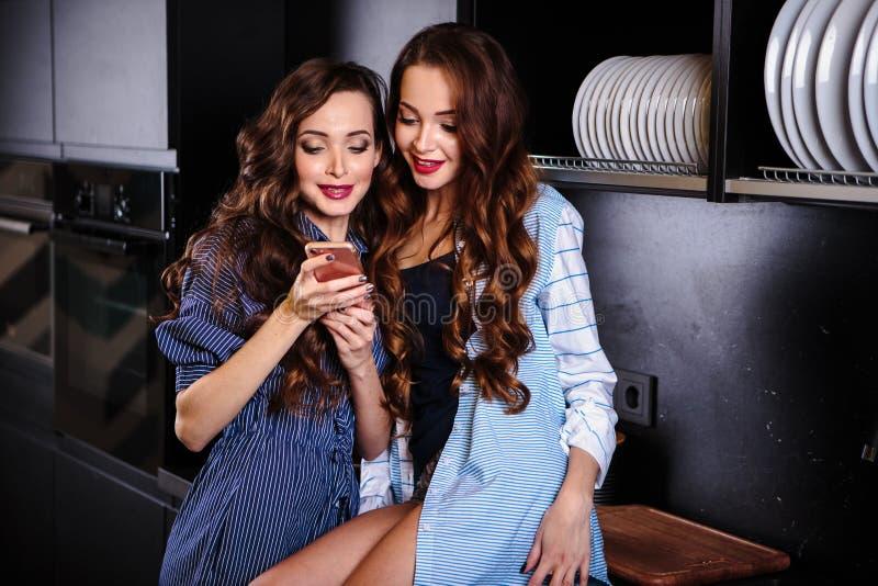 Милые молодые женщины близнецов совместно в комнате кухни делая фото на мобильном телефоне стоковая фотография rf