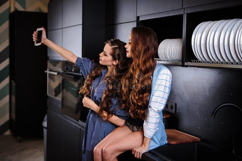 Милые молодые женщины близнецов совместно в комнате кухни делая фото на мобильном телефоне стоковые изображения rf