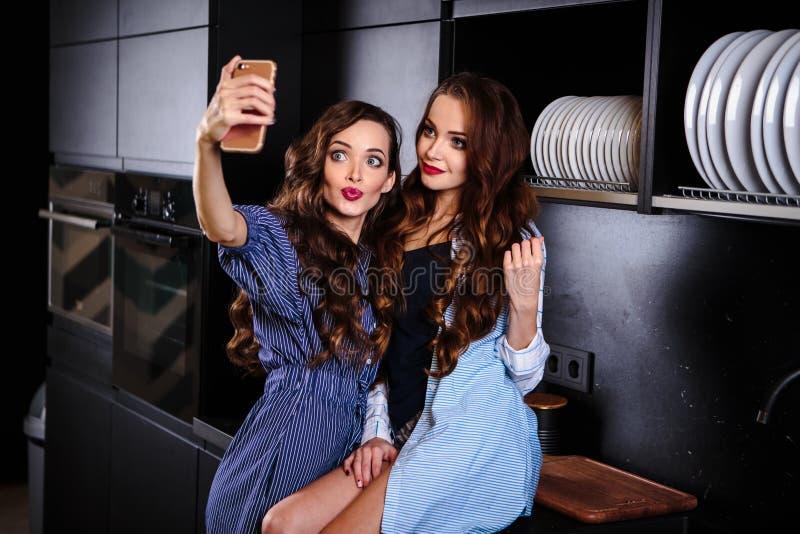 Милые молодые женщины близнецов совместно в комнате кухни делая фото на мобильном телефоне стоковое изображение