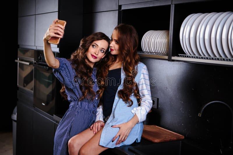 Милые молодые женщины близнецов совместно в комнате кухни делая фото на мобильном телефоне стоковые фотографии rf