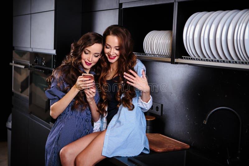 Милые молодые женщины близнецов совместно в комнате кухни делая фото на мобильном телефоне стоковое изображение rf