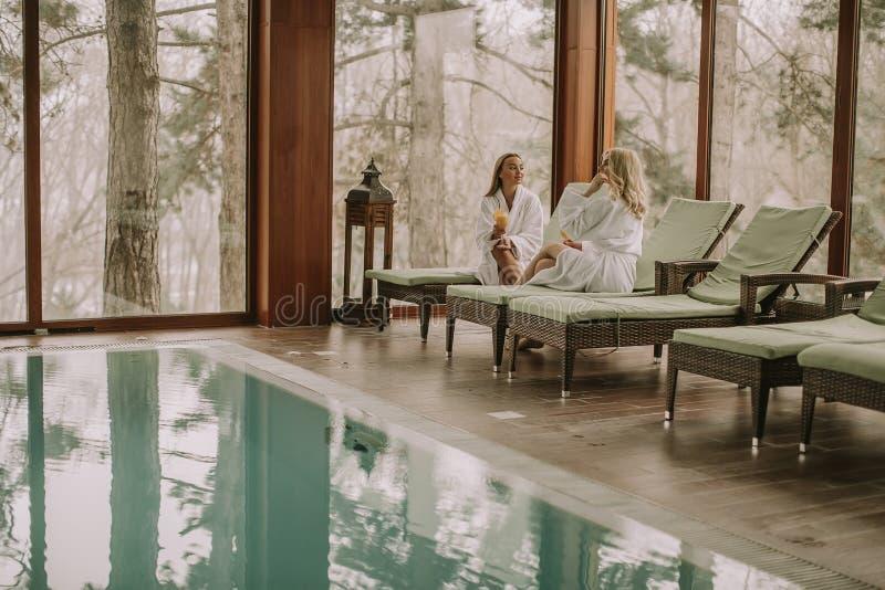 Милые молодые женщины ослабляя на deckchair плавая poo стоковое фото