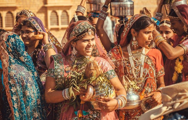 Милые молодые женщины разговаривая с подругами в толпе традиционного фестиваля пустыни стоковые фото
