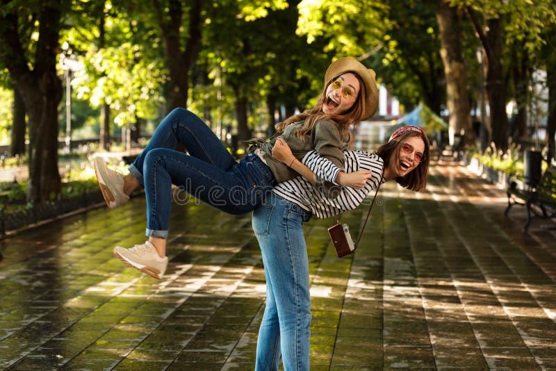 Милые молодые счастливые друзья женщин идя outdoors стоковое изображение