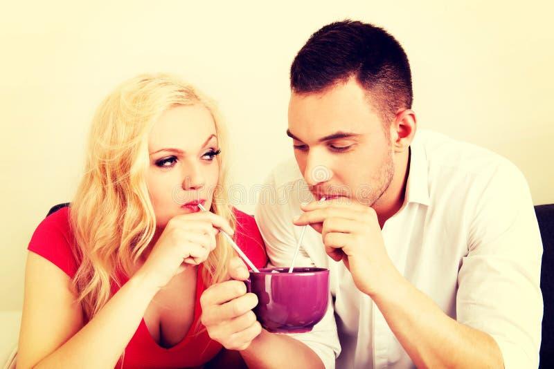 Милые пары выпивая от одной чашки стоковые изображения rf