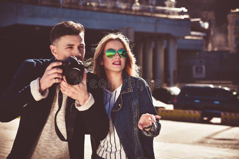 Милые пары в sunglass идя на улицу с камерой стоковая фотография