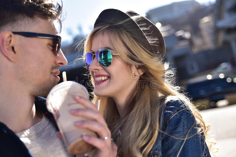 Милые пары идя на улицу и выпивают коктеили стоковые фотографии rf