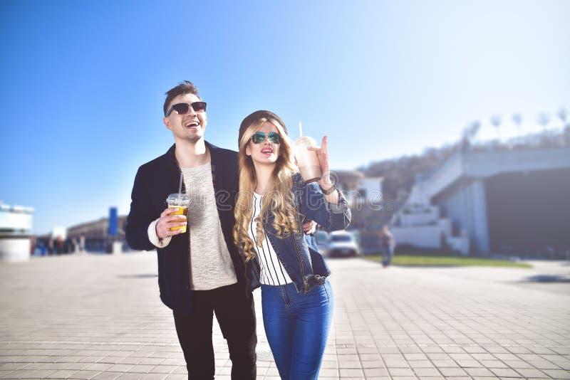 Милые пары идя на улицу и выпивают коктеили стоковые фото
