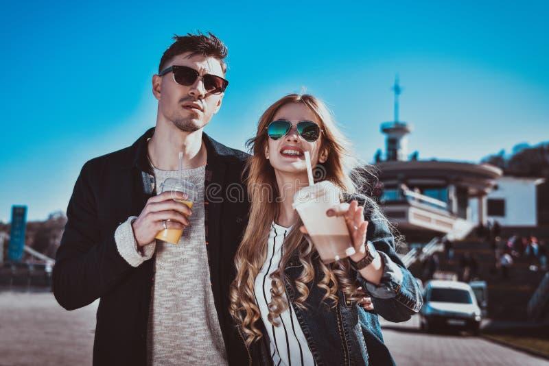 Милые пары имея потеху, идущ на улицу и выпивают коктеили стоковые изображения