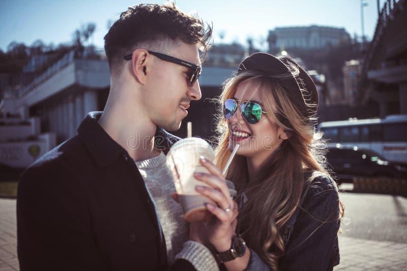 Милые пары имея потеху идя на коктеили улицы и питья стоковое фото rf
