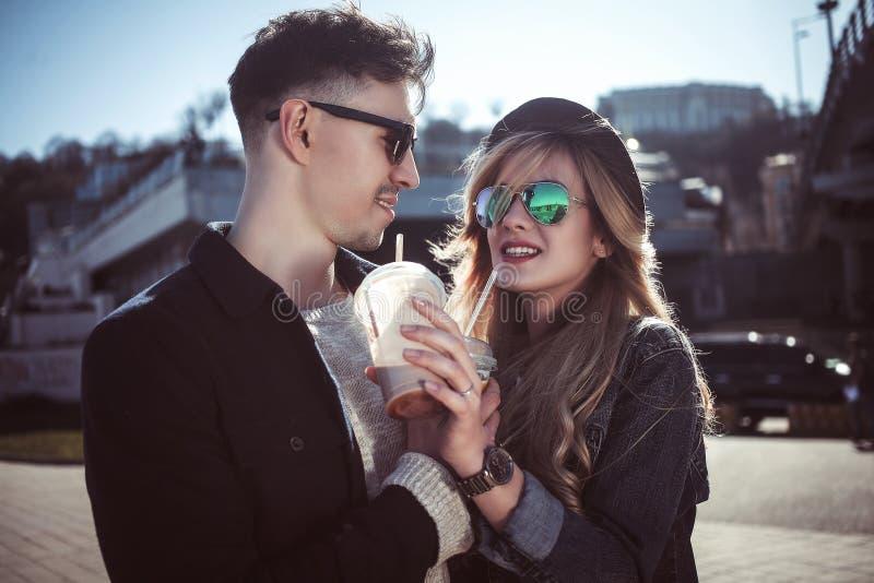 Милые пары имея потеху идя на коктеили улицы и питья стоковые изображения