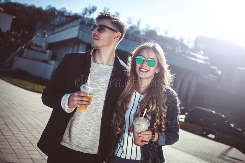 Милые пары имея потеху идя на коктеили улицы и питья стоковая фотография rf