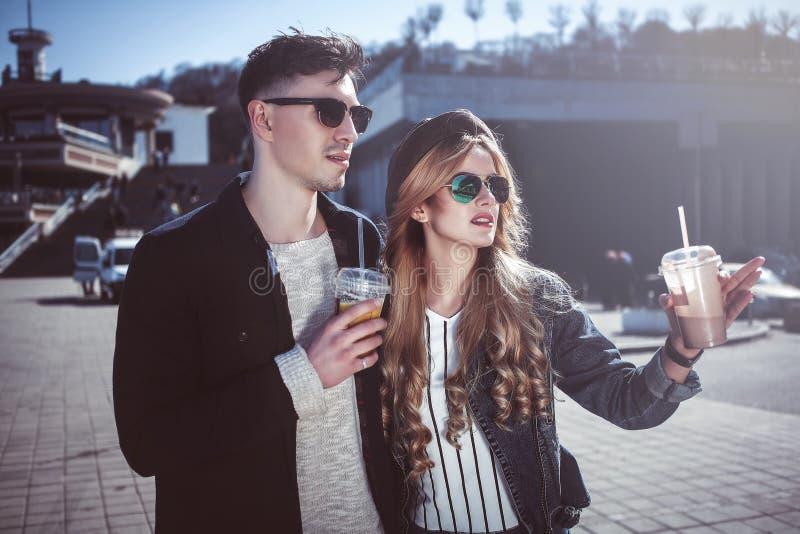 Милые пары имея потеху идя на коктеили улицы и питья стоковые изображения rf