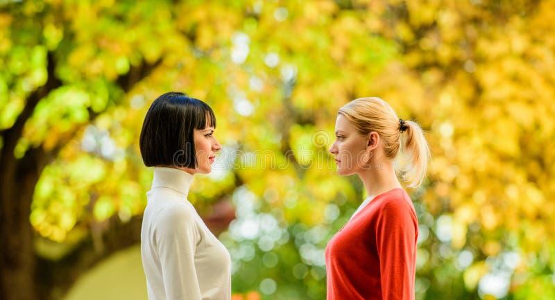 Милые сестры подруг Визуальный контакт Женщины смотря один другого с вниманием Белокурые конкуренты брюнета стоковое изображение
