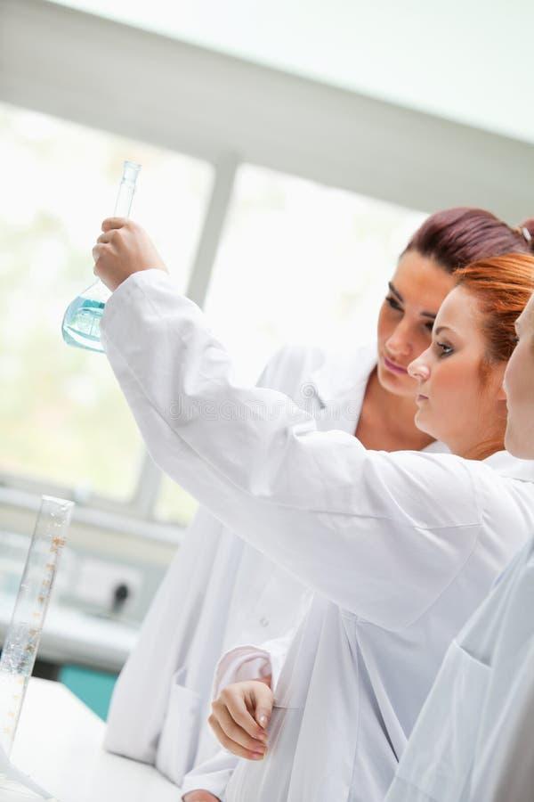 Милые студенты химии смотря жидкость стоковые фото
