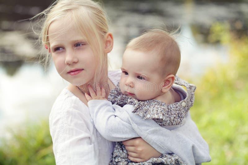 Милые eyears сестер на открытом воздухе 1 и 8 маленьких девочек старые стоковые фото