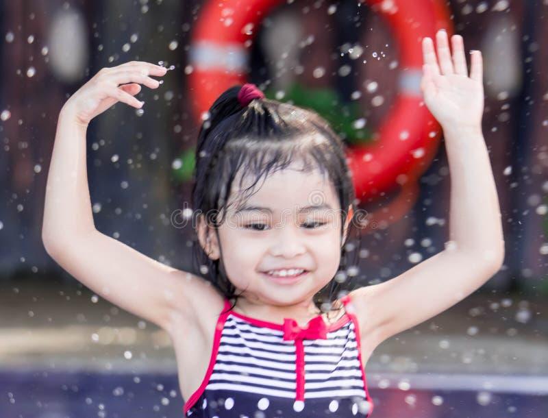 Милый азиатский женский ребенок малыша пока играющ и брызгающ воду в бассейне стоковое фото