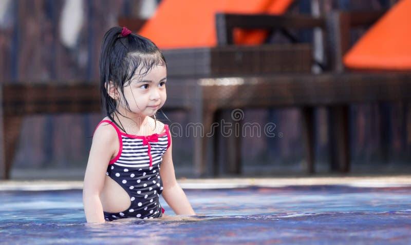 Милый азиатский женский ребенок малыша пока играющ на воде в бассейне стоковое изображение rf