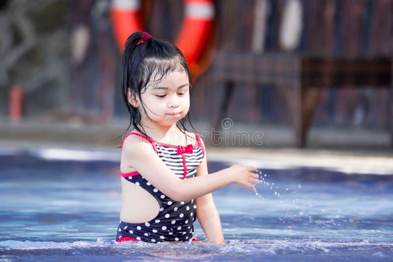 Милый азиатский женский ребенок малыша пока играющ на воде в бассейне стоковые фотографии rf