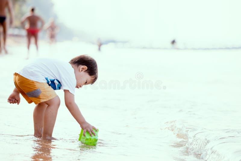 Милый азиатский мальчик маленького ребенка имея потеху, который нужно сыграть на пляже стоковая фотография rf