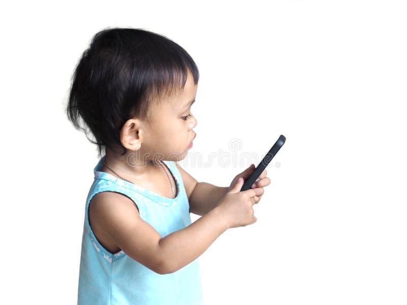 Милый азиатский ребёнок смотря умный телефон стоковая фотография