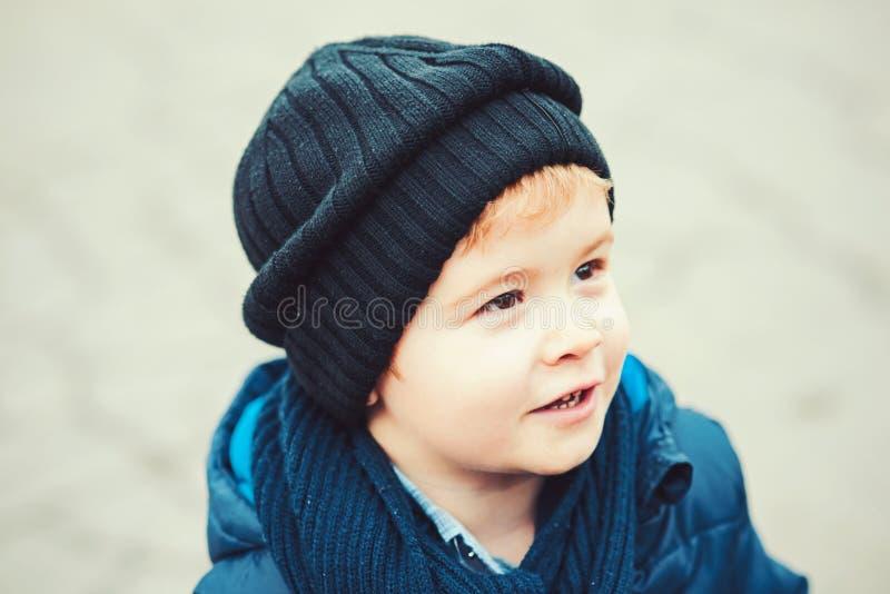 Милый белокурый мальчик в черной шляпе и голубом parka идя на улицу Портрет крупного плана милого ребенк outdoors стоковые фото