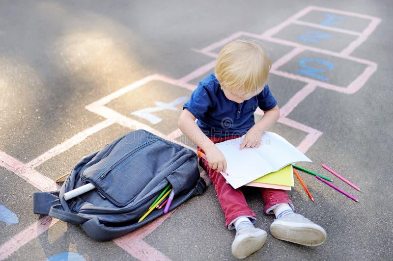 Милый белокурый мальчик делая домашнюю работу сидя на школьном дворе после школы при сумки кладя близко стоковое фото rf