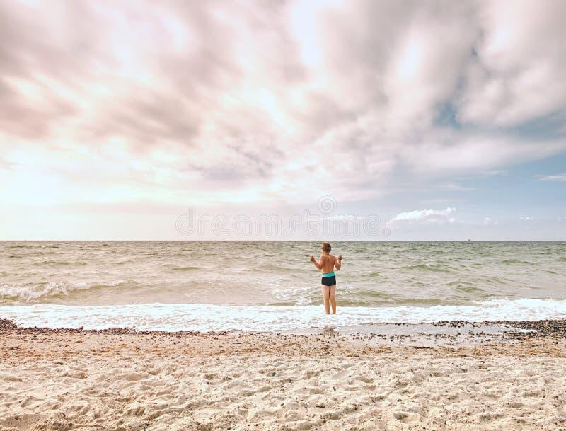 Милый белокурый белокурый мальчик идя на пляж в пенообразное море развевает Ветреный летний день, стоковое изображение rf