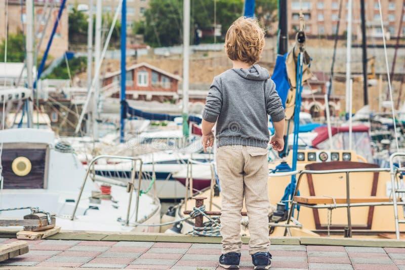Милый белокурый мальчик смотря яхты и парусники стоковое изображение rf