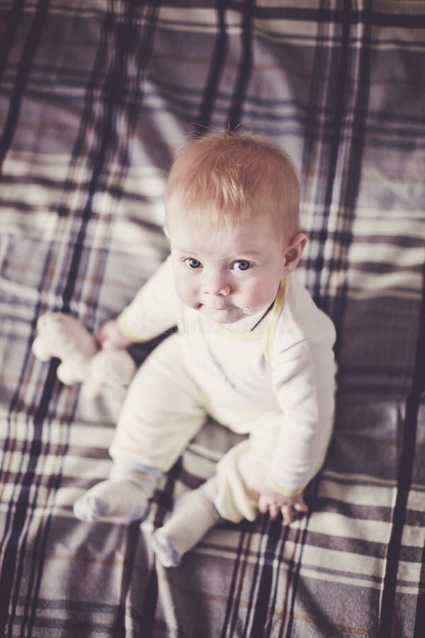 Милый белокурый младенец с голубыми глазами в светлых одеждах сидит на покрывале шотландки на кровати и смотрит вверх стоковые фотографии rf