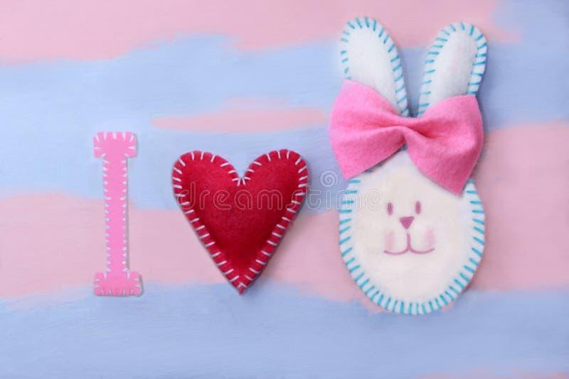 Милый белый зайчик пасхи сделал из войлока с розовым смычком на розов-голубой предпосылке с пестроткаными цветками Handmade от во стоковое изображение
