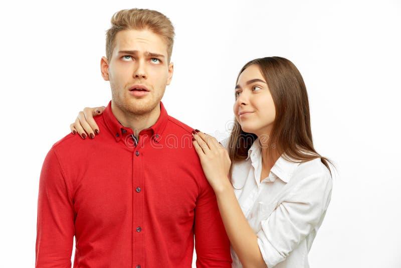 Милый брюнет в белой рубашке обнимает и успокаивает ее товарища - молодой человека со светлыми волосами которые свертывают глаза  стоковые фотографии rf