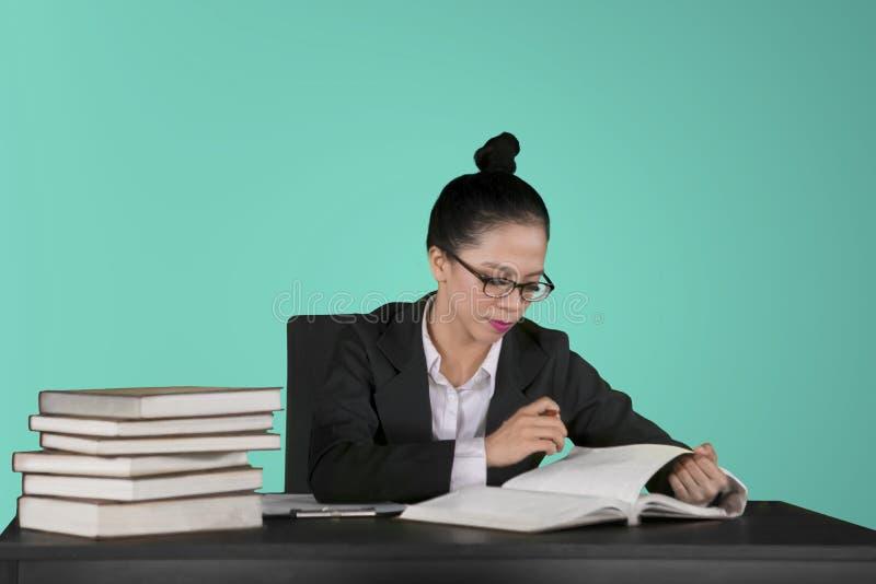 Милый бухгалтер проверяя документ на студии стоковое фото