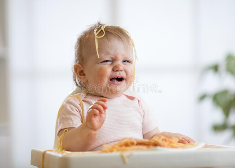Милый грязный младенец плача пока ел макаронные изделия дома стоковое изображение