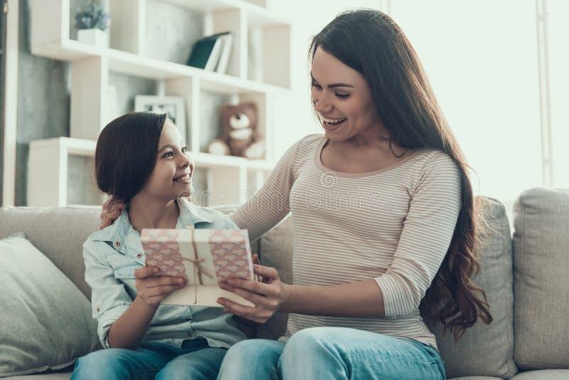 Милый давать маленькой девочки присутствующий к молодой женщине стоковое изображение