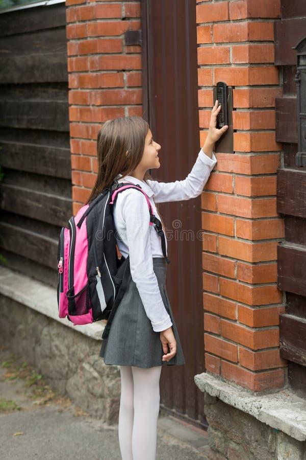 Милый девочка-подросток звеня в дверном звоноке дома после идти к школе стоковые фото