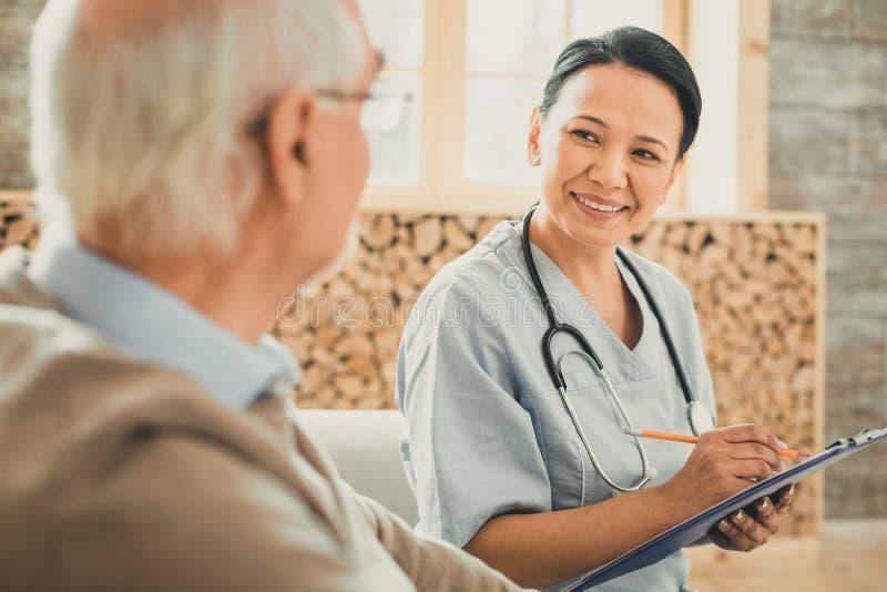Милый доктор со стетоскопом на ее шеи перечисляя жалобы стоковые фото