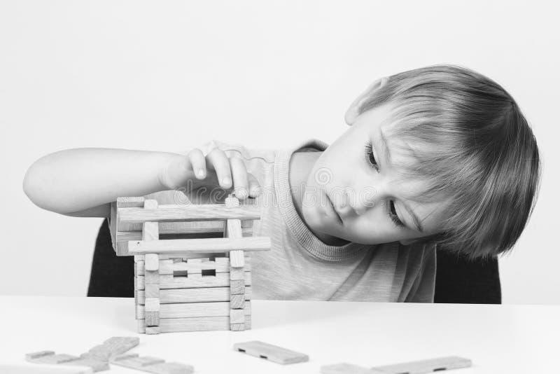 Милый дом здания мальчика от деревянных блоков Ребенк имеет идею построить дом детство счастливое стоковое фото