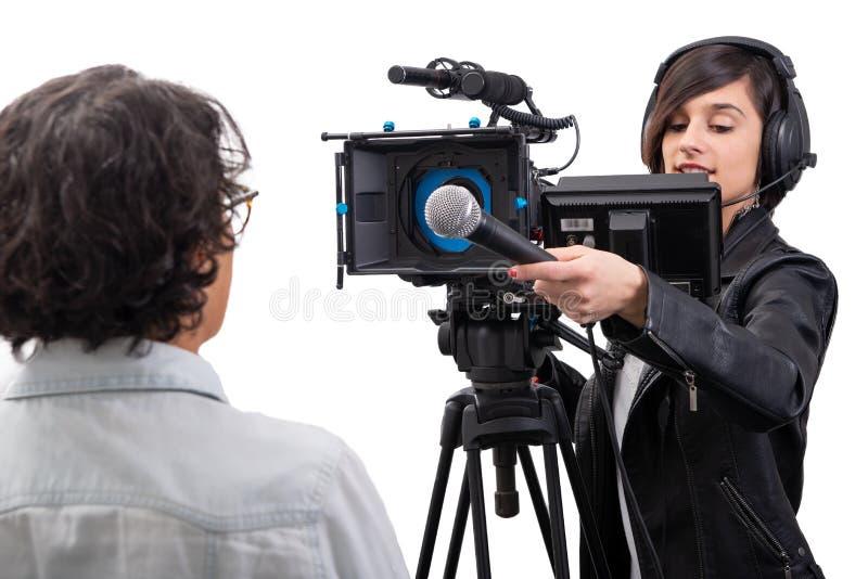 Милый журналист молодой женщины с микрофоном с видеокамерой на белизне стоковые фотографии rf