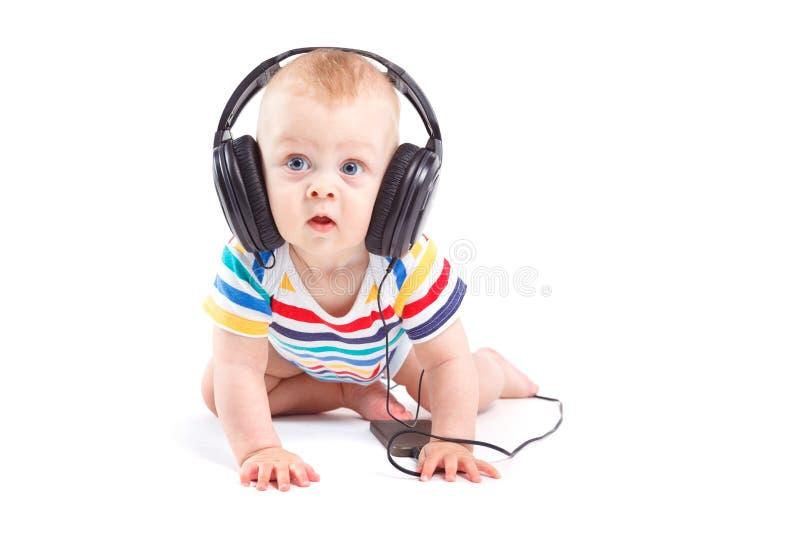 Милый изумленный мальчик в красочной рубашке с наушниками на голове стоковые изображения rf