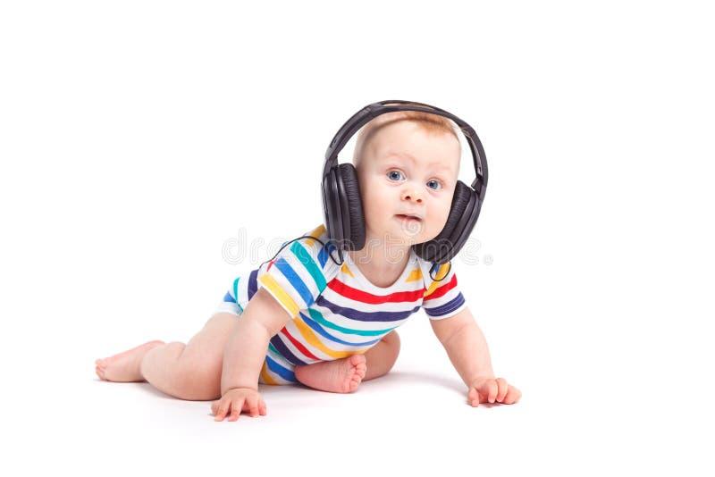 Милый изумленный мальчик в красочной рубашке с наушниками на голове стоковое изображение