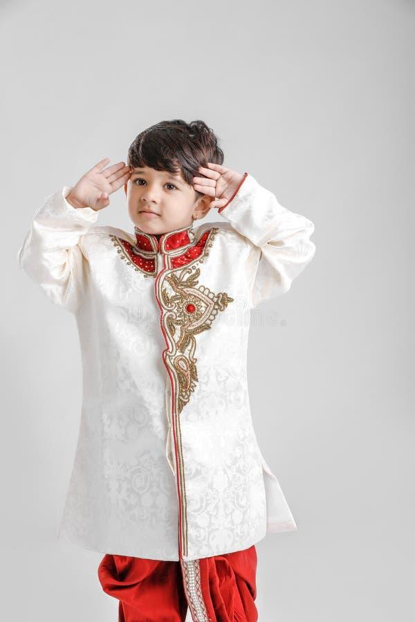 Милый индийский/азиатский мальчик в этнической носке и салютуя национальном флаге стоковое изображение rf